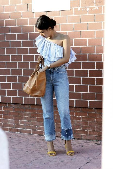 Chica usando una camisa sin hombro y unos blue jeans color azul