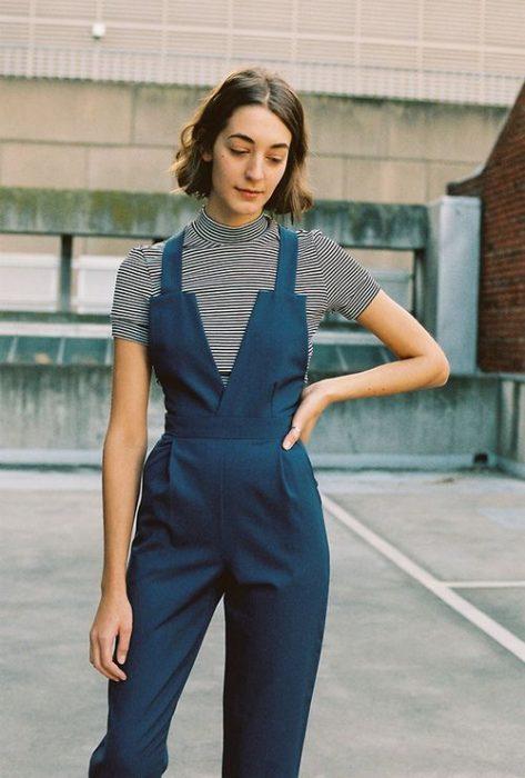 chica usando un overol azul marino con blusa a rayas