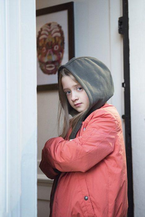 Niña que quiere ser modelo de Zara Boys posando con una chamarra de la marca