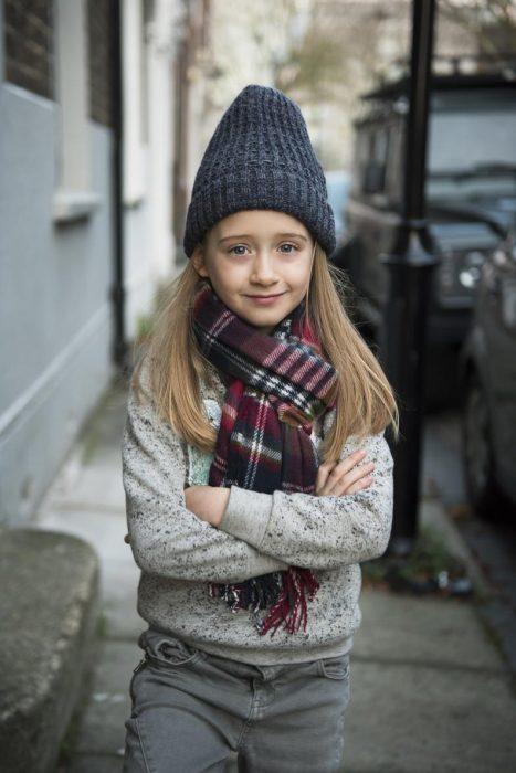 Niña que quiere ser modelo de Zara Boys posando con una bufanda sueter y pantalón de la marca