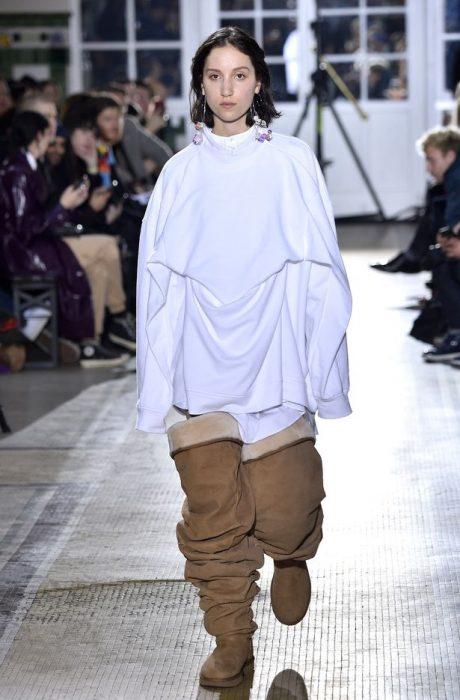 Chica desfilando en la semana de la moda en París usando unas botas Uggs hasta el muslo y usando una suadadera blanca extra larga