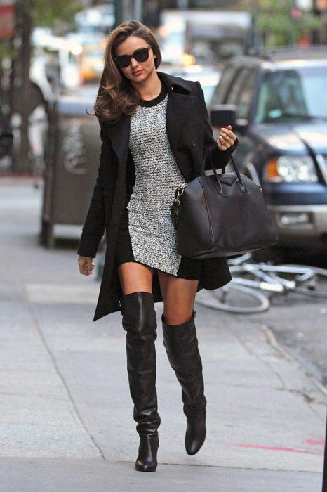 Miranda Kerr usando un vestido gris y saco negro con unas botas hasta el muslo mientras camina por una calle de Los Ángeles