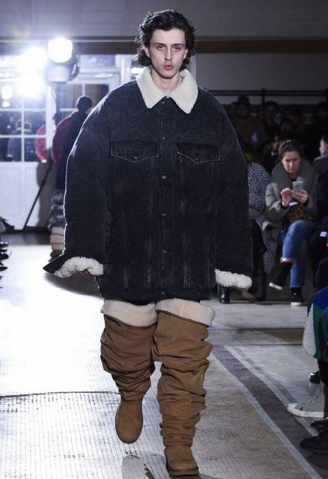Chico desfilando en una pasarela durante la semana de la moda en parís usando unas botas ugg hasta el muslo