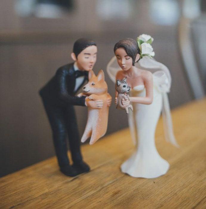 Muñecos de pastel que son una replica de los novios y sus mascotas