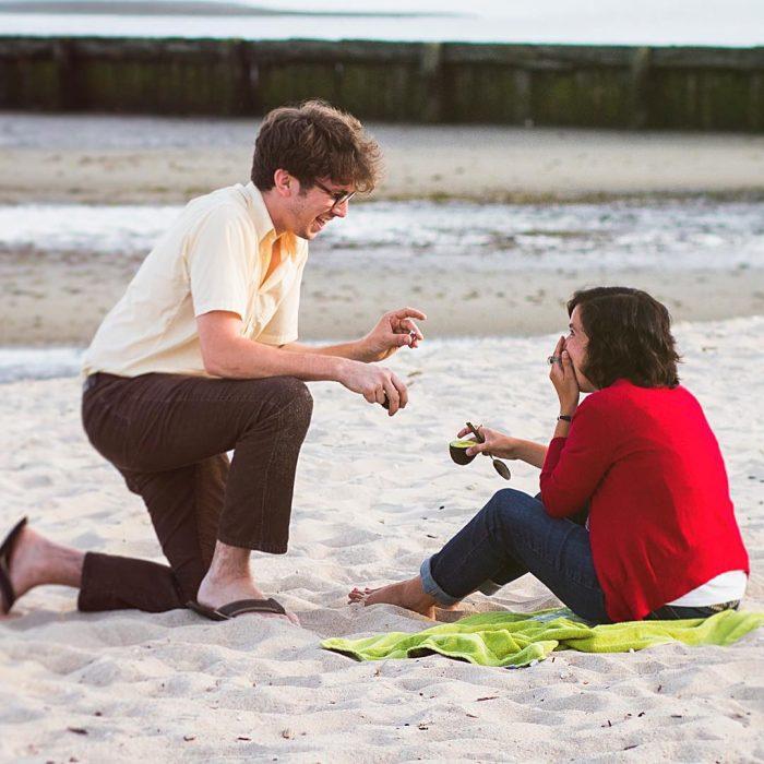 Chico proponiendole matrimonio a su novia en un a playa