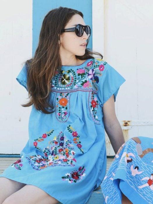chica con vestido azul bordado