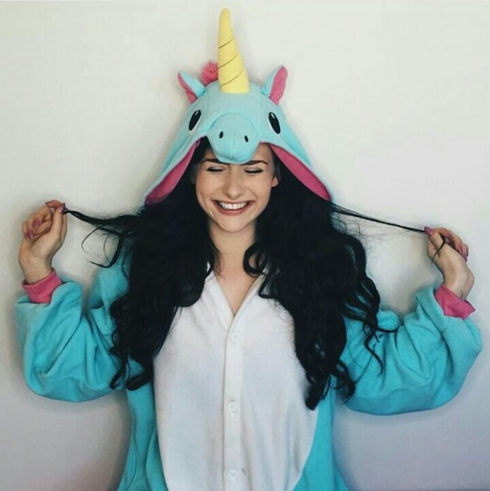 Chica usando una pijama en forma de unicornio