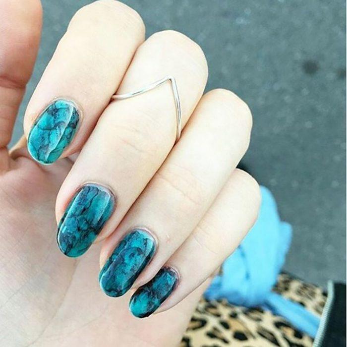 Manicura de uñas color azul turquesa y mármol