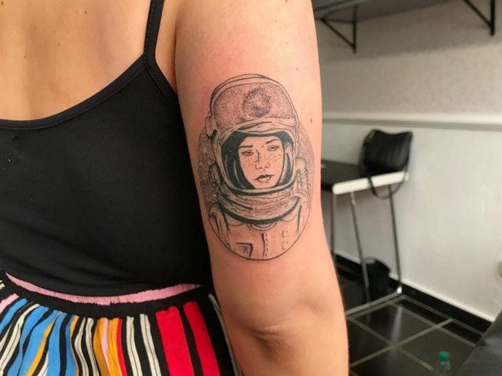 Chica con el tatuaje de una astronauta en su brazo