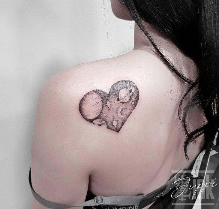 Chica con un corazón que tiene el universo como tatuaje