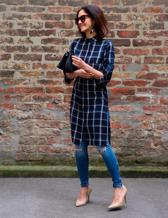 Chica usando un vestido sobre vaqueros mientras camina por la calle