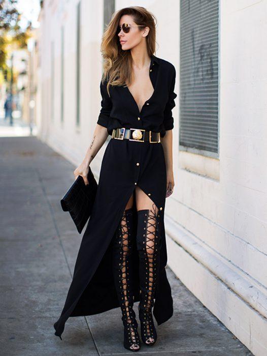 Chica usando un vestido largo y negro con botas atadas hasta los muslos