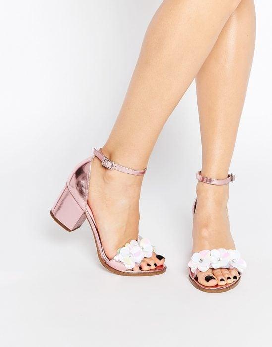 Chica usando unos zapatos elegantes con aplicaciones de flores en color rosa