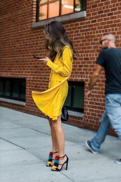 Chica usando un vestido amarillo y zapatos elegantes en color negro con aplicaciones de pompones en color azul rojo y amarillo