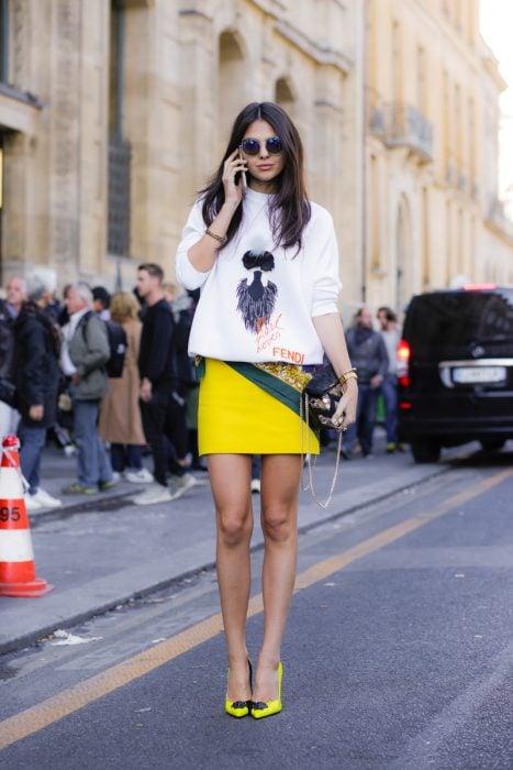 Chica usando unos zapatos amarillos con pompones junto a una falda amarilla y blusa de color blanco