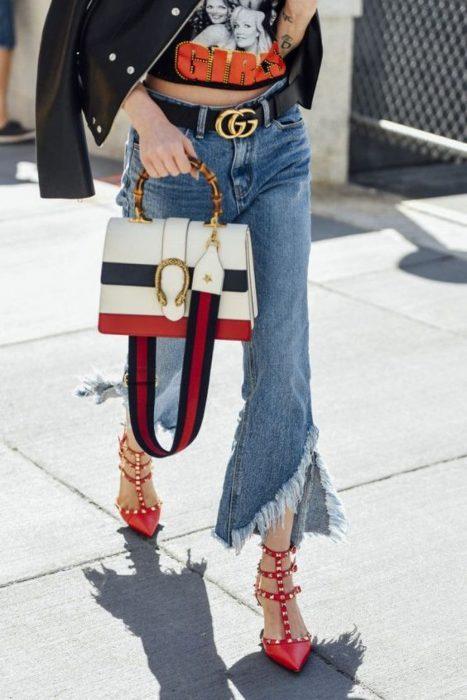 Chica usando unos zapatos en color rojo con estoperoles pantalones anchos y bolso gucci