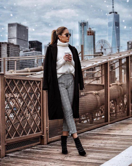 Chica usando botines en color negro con pantalones gris y abrigo de color negro