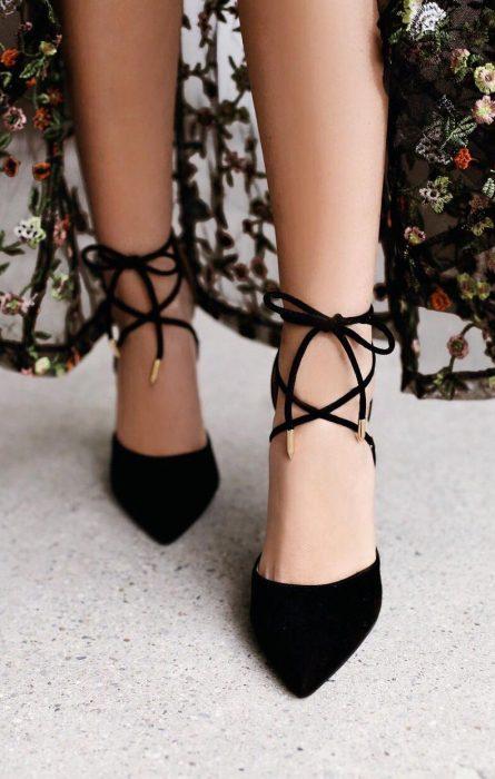 Chica usando unos zapatos negros con correas atadas en un moño