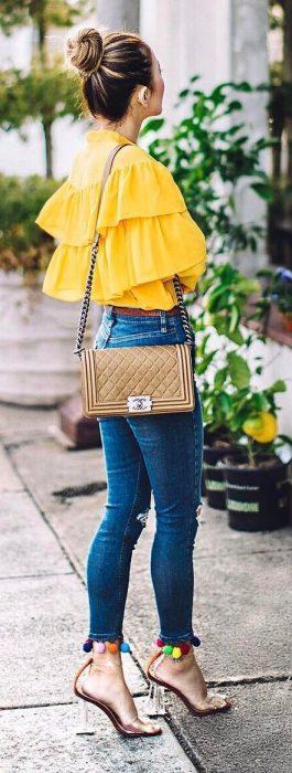 Chica usando unos zapatos elegantes con pompones y tacón transparente