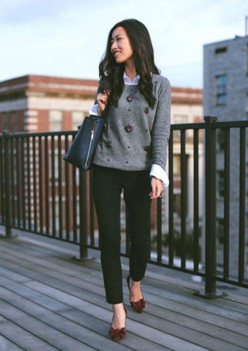 Chica usando una súeter de color gris leggings negros y zapatos elegantes con un moño rojo