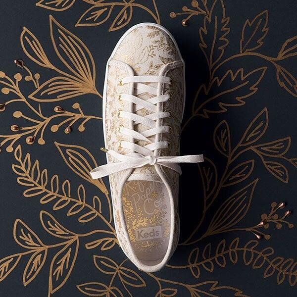 Zapatos blancos con líneas en color dorado