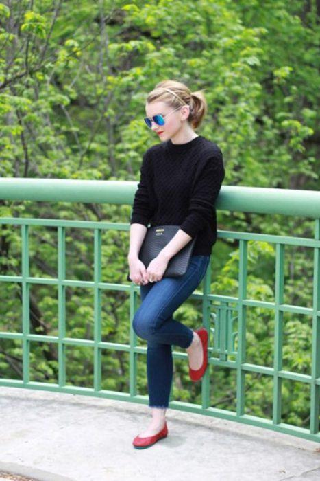 Chica recargada en una cerca usado una chaqueta negra, pantalón y zapatos rojos