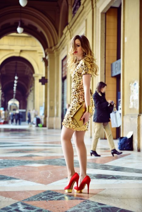 Chica posando para una sesión de fotos usando un vestido amarillo y zapatos rojos