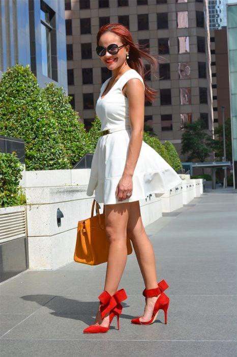 Chica usando un vestido blanco con zapatos rojos y bolso de color mostaza