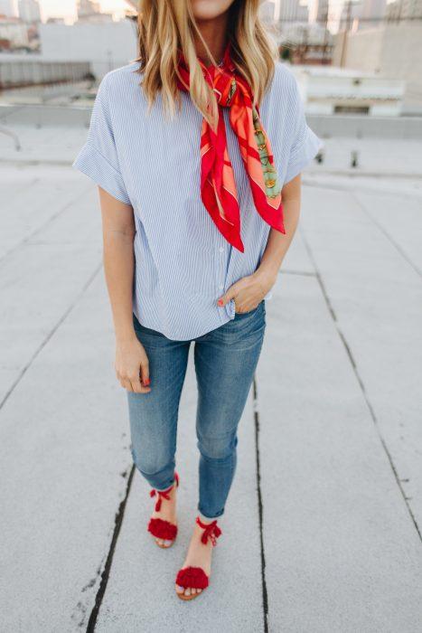 Chica usando un pañuelo rojo sobre el cuello mientras viste de mezclilla y unos zapatos rojos