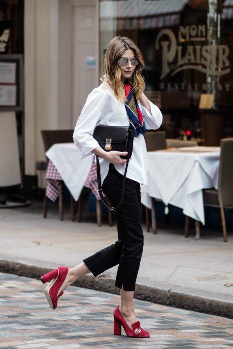 Chica caminando por la calle usando un atuendo blanco y negro con unos zapatos cuadrados de color rojo