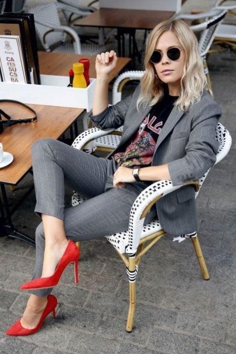 Cara Delevigne sentada usando un traje gris con zapatos color rojo
