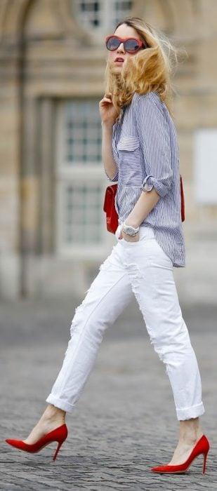 Chica caminando por las calles mientras usa un pantalón blanco, zapatos rojos y blusa color azul