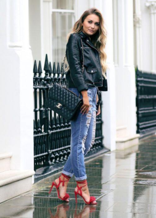 Chica parada en la calle usando un pantalón de mezclilla, chaqueta de cuero y zapatos rojos