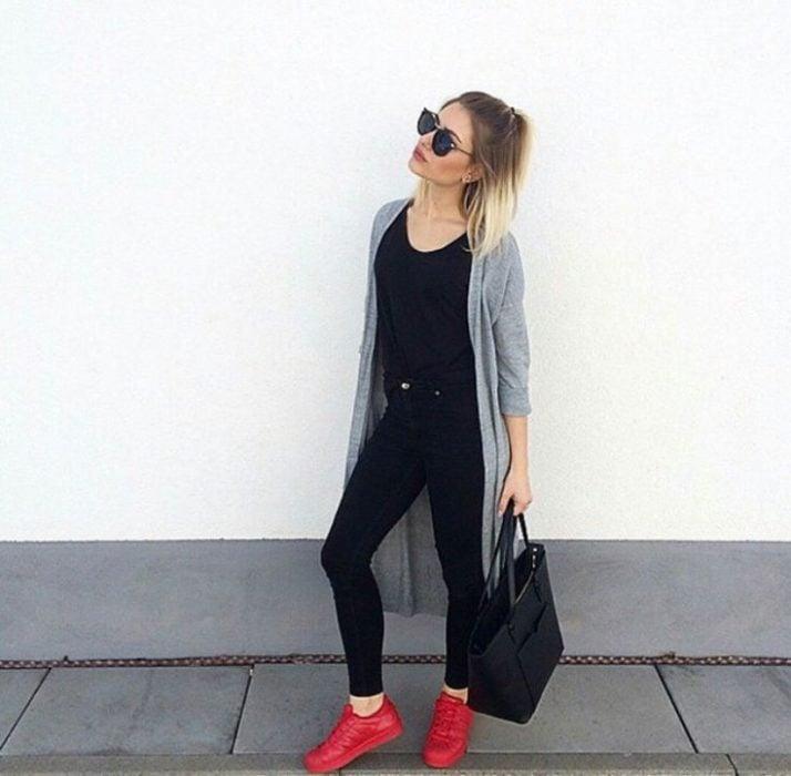 Chica parada sobre una pared usando un atuendo en negro y tenis de color rojo