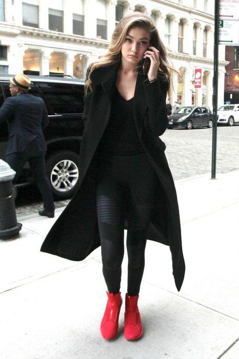 Gigi Hadid caminando mientras habla por celular usando un atuendo en nengro y botas de color rojo