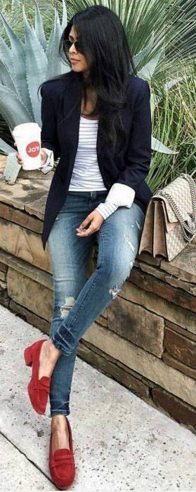Chica sentada sobre una banca usado un outfit de mezclilla y zapatos rojos