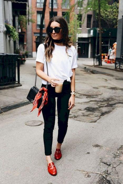 Chica caminando por la calle usando un outfit blanco y negro con zapatos rojos
