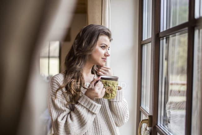 Chica tomando una taza de café mientras está mirando por la ventana