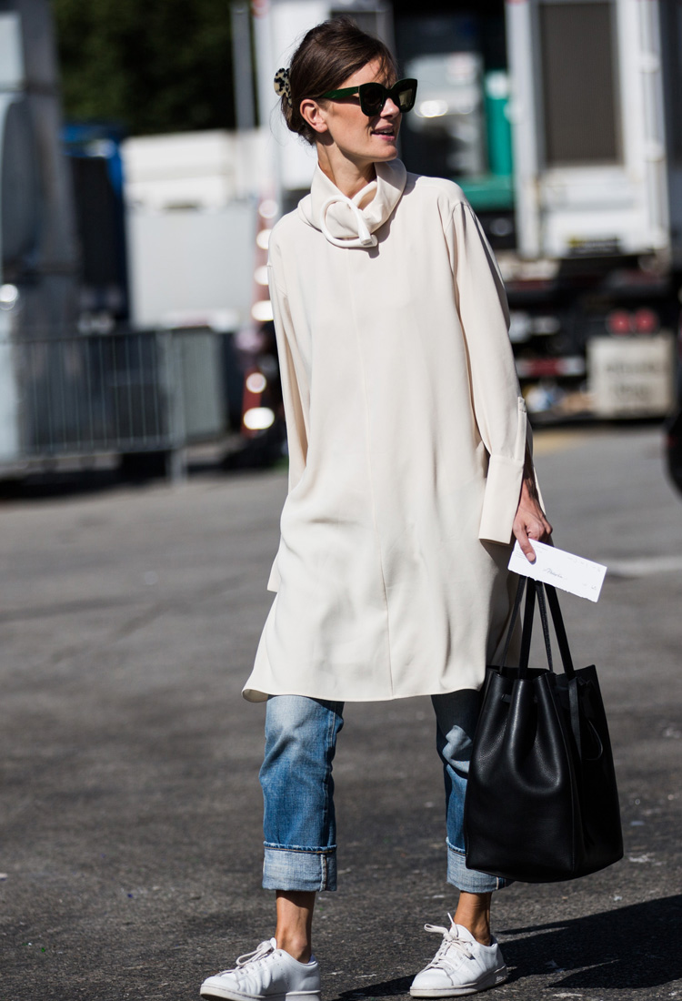 3e79fa8a3b4 Chica usando un vestido sobre vaqueros mientras camina por la calle