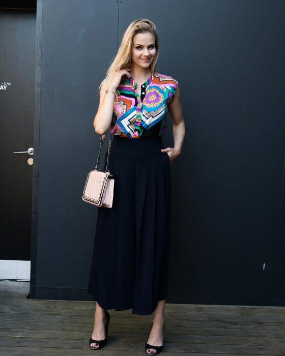 mujer con blusa de estampado colorido y falda negra