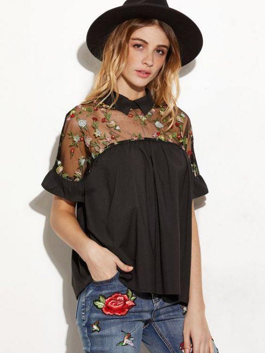 chica usando blusa negra con bordado de flores
