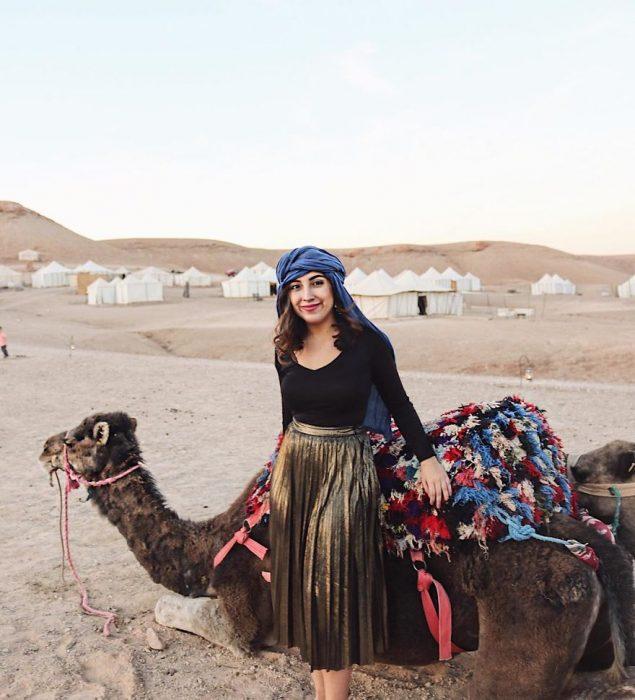 chica frente a un camello en el desierto