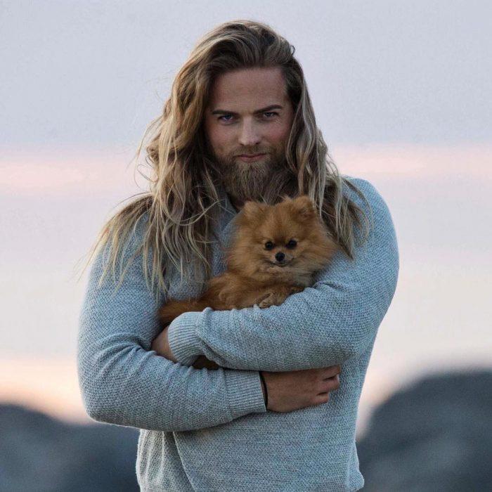 chico musculoso abrazando a un perro