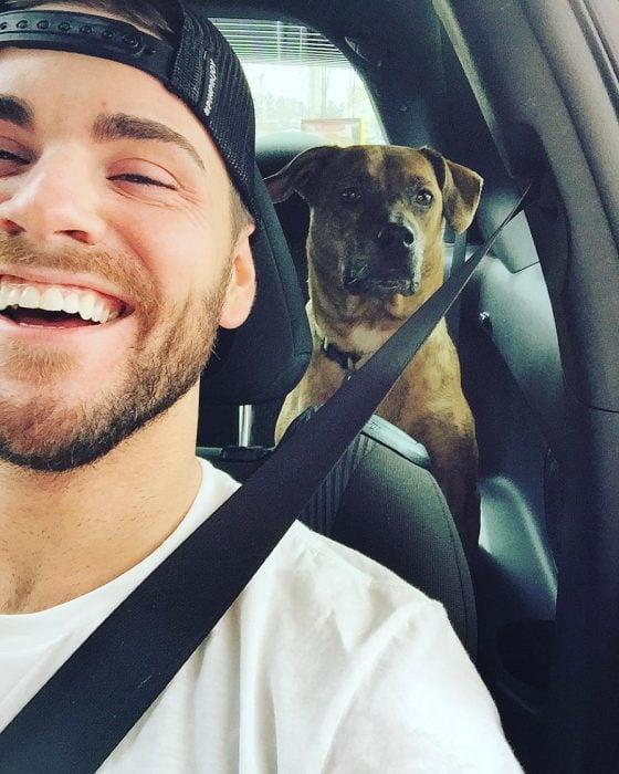 chico paseando a su perro en el auto
