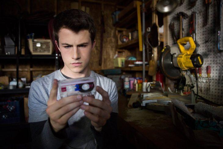 chico con una cinta de audio en la mano