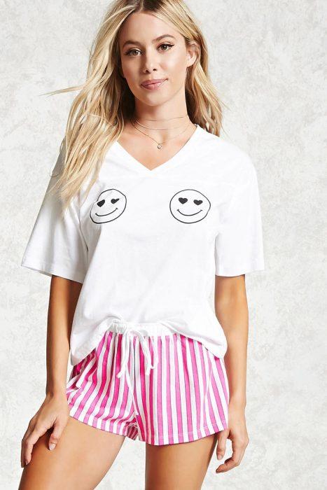 Chica usando una pijama de short rosa y camisa blanca