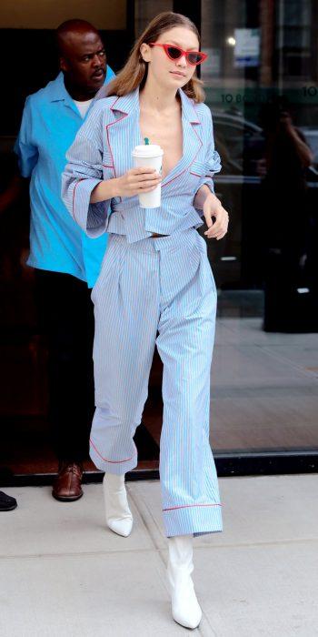 Gigi Hadid usando una pijama azul con botas blancas