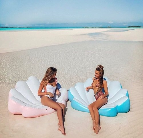 chicas en flotadores en forma de conchas de mar