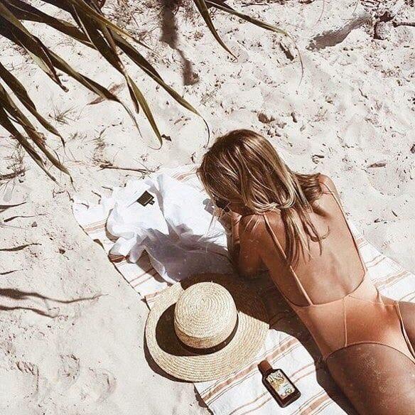 chica en la playa tomando el sol