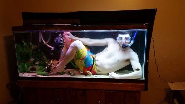 Chico dentro de una pecera nadando